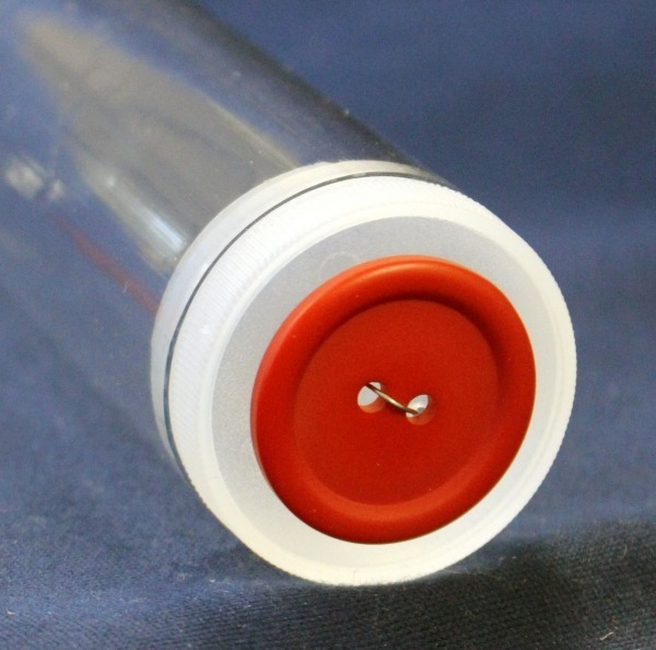 Button display tube with red button attached