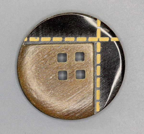 Brown horn button with yellow stitching
