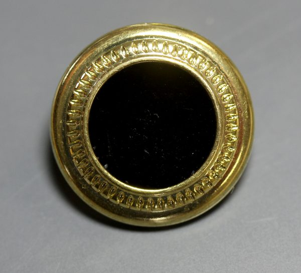 gold metal button with black center