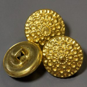 Three golden metal buttons with one showing shank back